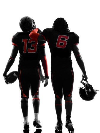 african american silhouette: two american football players walking rear view in silhouette shadow on white background