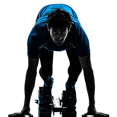 één mens loper sprinter op startblokken in silhouet studio geïsoleerd op witte achtergrond