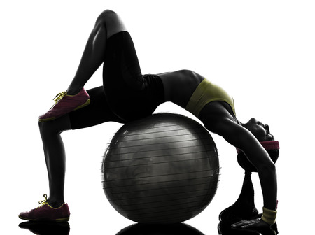 supple: one supple woman exercising fitness workout on fitness ball in silhouette on white background