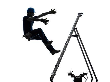 accidente trabajo: un hombre trabajador manual que cae de la escalera en silueta sobre fondo blanco Foto de archivo