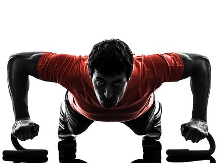 een man te oefenen fitness workout push ups in silhouet op een witte achtergrond Stockfoto
