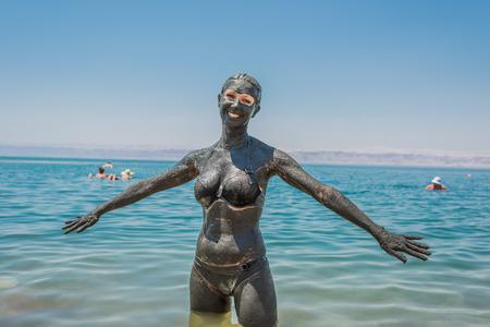 Jordan で死海の泥のボディケア ・ トリートメントを適用する 1 つの女性