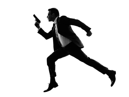 one caucasian man running with handgun in silhouette on white  Stockfoto