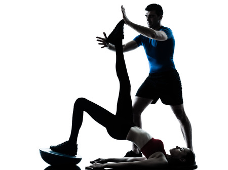 personal trainer man coach and woman exercising abdominal push ups on bosu silhouette studio isolated on white