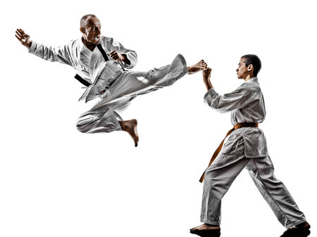two karate men sensei and teenager student fighters fighting isolated on white  photo