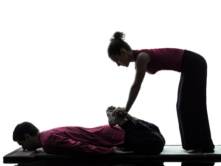 one man and woman performing feet legs thai massage in silhouette studio on white