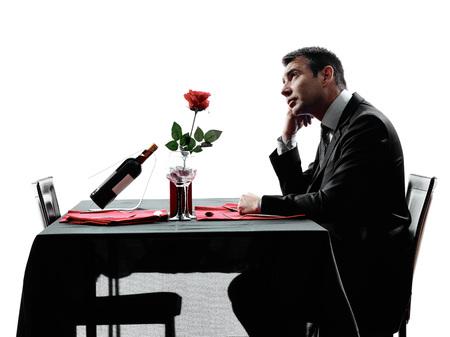 hombre solitario: un hombre esperando comedor en siluetas en el fondo blanco Foto de archivo