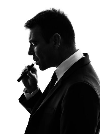 background e cigarette: one caucasian business man smoking electronic e-cigarette in silhouette on white background Stock Photo