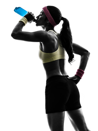 one woman exercising fitness drinking energy drink in silhouette on white background Stock Photo