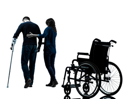 healing: one man injured man with woman walking away from wheelchair with crutches in silhouette studio on white background