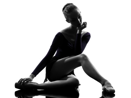 ballet dancer: one  young woman ballerina ballet dancer stretching warming up in silhouette studio on white background Stock Photo