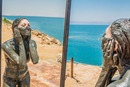 mud woman: one  woman applying Dead Sea mud for body care treatment in Jordan
