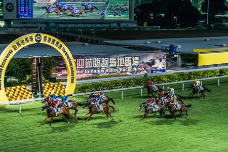 caballos corriendo: Happy Valley, Hong Kong, China - 5 de junio 2014: carrera de caballos en el hipódromo de Happy Valley