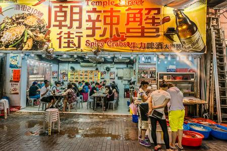 Kowloon, Hong Kong, China- June 8, 2014: people outside seafood restaurants in the Temple street night market Tsim Sha Tsui