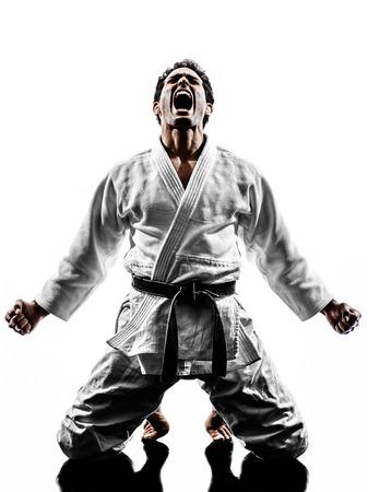 judo: un hombre luchador judoka en silueta sobre fondo blanco