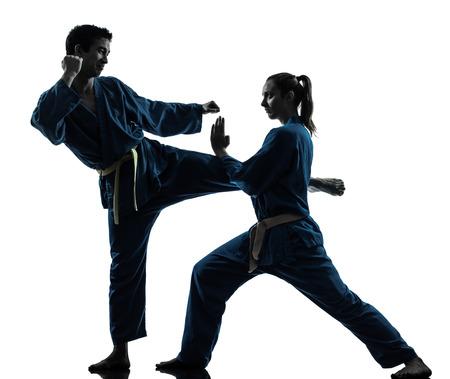 defensa personal: un hombre mujer Pareja ejercicio artes marciales del karate vietvodao en estudio de la silueta aislado en el fondo blanco Foto de archivo