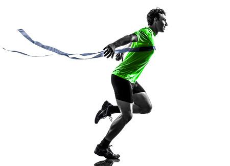 一人の男若いスプリンター ランナーを勝者シルエット スタジオでフィニッシュ ラインに白い背景の上