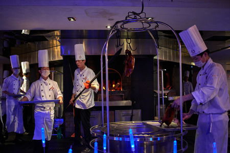 Beijing , China - September 23, 2014 : cooks chefs preparing traditional Chinese Roast Duck cooking at tha famous Dadong restaurant Beijing China
