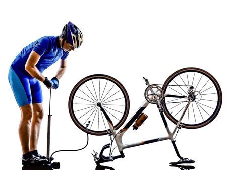cyclist repairing bicycle in silhouette on white background photo