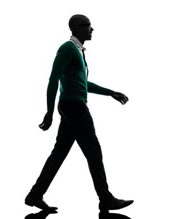 people walking: one african black man walking in silhouette studio on white background