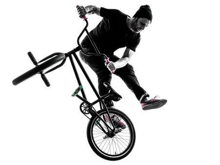 silueta ciclista: un hombre haciendo ejercicio figura bmx acrobático en estudio de la silueta aislado en el fondo blanco