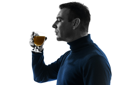 side profile: one  man drinking orange juice portrait in silhouette studio isolated on white background