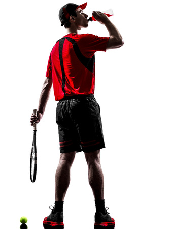 energy drinks: one young man tennis player drinking energy drinks in silhouette isolated on white background