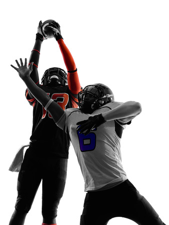 two american football players pass action in silhouette shadow on white background photo