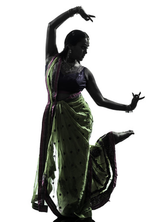 bollywood: one indian woman dancer dancing in silhouette studio isolated on white