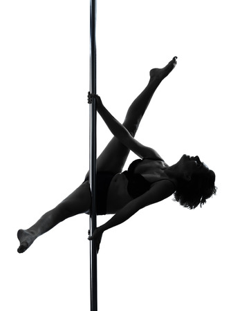 pole dance: one  woman pole dancer dancing in silhouette studio isolated on white