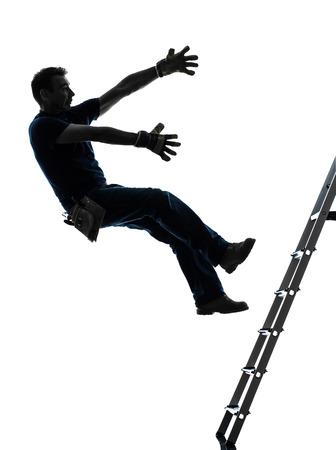 hombre cayendo: un hombre trabajador manual que cae de la escalera en silueta sobre fondo blanco Foto de archivo