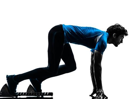 starting blocks: one  man runner sprinter on starting blocks in silhouette studio isolated on white background