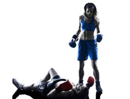 fighting arts: one woman boxer boxing one man  kickboxing in silhouette isolated on white background