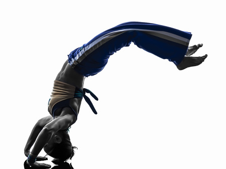 BACKFLIP: one  woman capoeira dancer dancing in silhouette studio isolated on white background Stock Photo