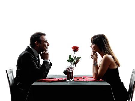 siluetas de enamorados: parejas amantes dinning en siluetas en el fondo blanco Foto de archivo