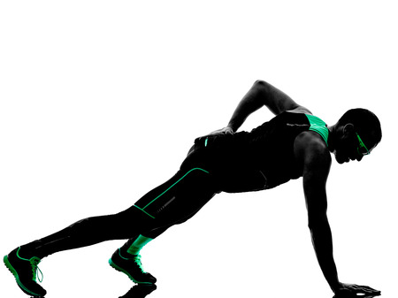 one man exercising push ups fitness  in silhouette isolated on white background Stock Photo
