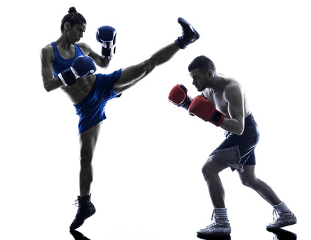thai boxing: one woman boxer boxing one man  kickboxing in silhouette isolated on white background