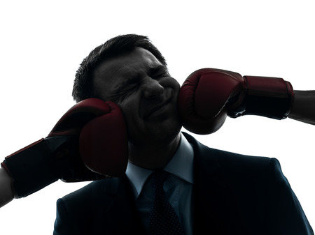 agression: one  businessman punch by boxing gloves in silhouette studio isolated on white background