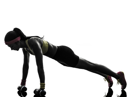 pushups: one woman exercising fitness workout push ups in silhouette on white background