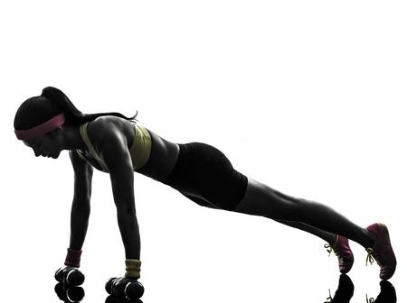 silueta humana: Una mujer de entrenamiento de la aptitud ejercicio flexiones en silueta sobre fondo blanco Foto de archivo