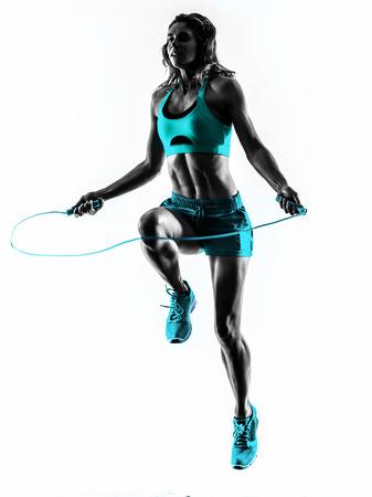 gimnasio mujeres: una mujer cauc�sica ejercicio de salto de la aptitud de la cuerda en la silueta del estudio aislada en el fondo blanco Foto de archivo