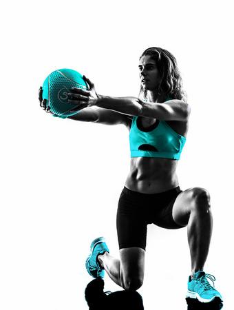 deporte: una mujer cauc�sica que ejercita la bola de medicina de la aptitud en el estudio de la silueta aislado en el fondo blanco Foto de archivo