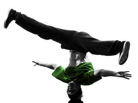 breakdancing: one  young acrobatic break dancer breakdancing man in silhouette white background