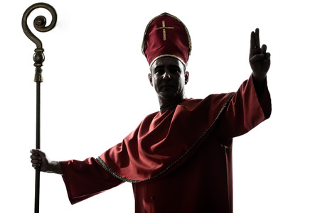 human silhouette: one man cardinal bishop silhouette saluting blessing in studio isolated on white background