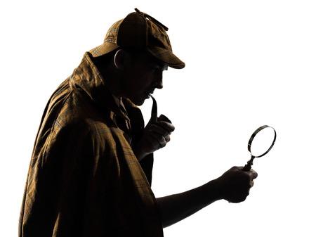 lupa: silueta detective en el estudio sobre fondo blanco