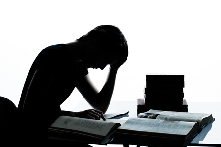 one  young teenager silhouette boy girl studying tired reading books in studio cut out isolated on white background photo