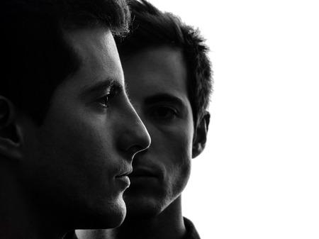 gemelas: cerca retrato de dos hombres jóvenes en la sombra fondo blanco