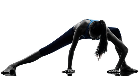 warm up: one  woman exercising yoga stretching legs warm up in silhouette studio isolated on white background