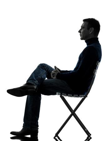 personas sentadas: un hombre sentado mirando de larga duraci�n en estudio de la silueta aislado en el fondo blanco Foto de archivo