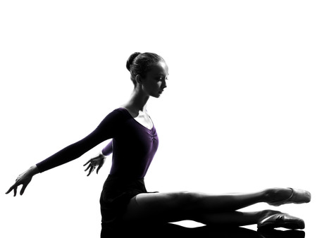 ballerina silhouette: one  young woman ballerina ballet dancer stretching warming up in silhouette studio on white background Stock Photo